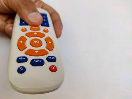 Remote control in hand for Television and set top box , Isolated on white Back ground Selective focus.
