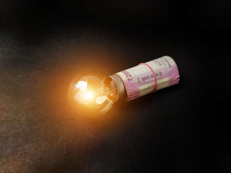 Financial innovation idea, creative solutions depicted by glowing light bulb and money bank notes Stock fotó
