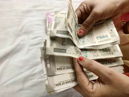 money notes counting by woman hands , indian rupees notes and coins background