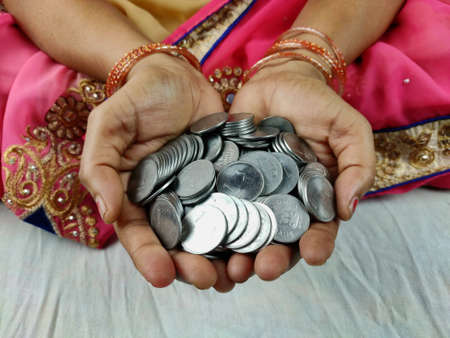 Woman hands full of indian coins , Selective Focus.