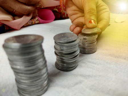 counting coins by stacking, woman hands holding coin