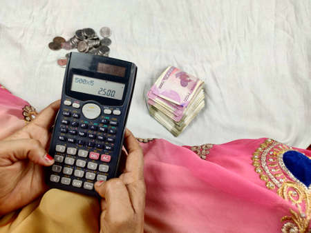 Indian woman counting bank notes using calculator