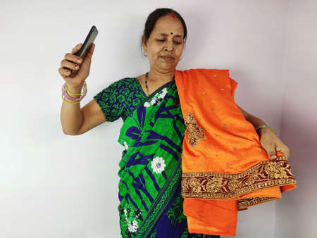 Woman showing new gifted sari on mobile video call to family and friends , thanks giving concept. Indian woman in talking on smart phone.