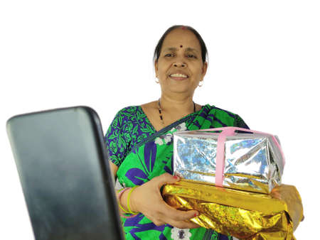 Indian Woman celebrate birthday or anniversary during video or phone call on mobile at home holding gift box present.