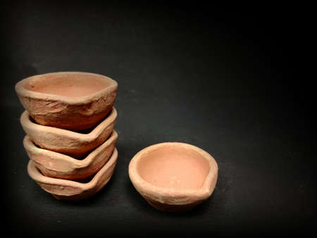 Mud clay diya arranged on black background, stack of diya Stock fotó