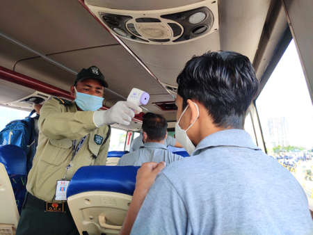 Noida, India- 11 September 2020 :Thermal scanning of bus passenger by security guards preventive measures to control spread of covid-19 virus.