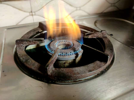 Burning blue and yellow gas stove on a kitchen background. Gas burner on the stove close-up