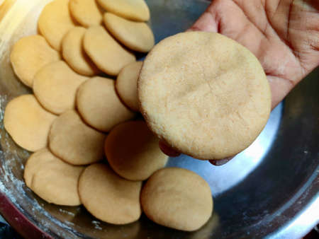 Wheat dough in hands of woman making round rolls for roti or bread making.