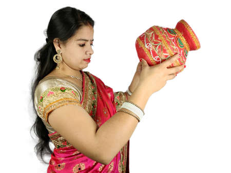 Decorated Earthen pot and coconut in hand on woman