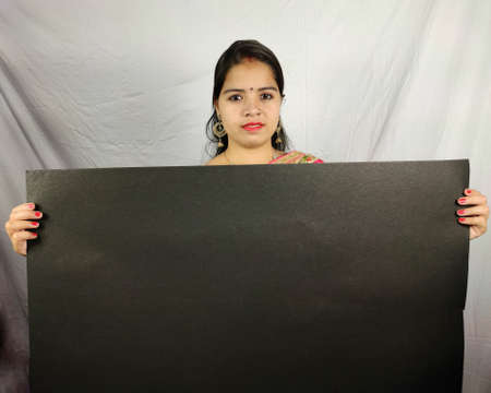 indian woman holding black poster Billboard on white background
