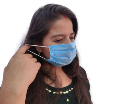 Woman wearing surgical face mask for protection from COVID and pollution side view on white background.