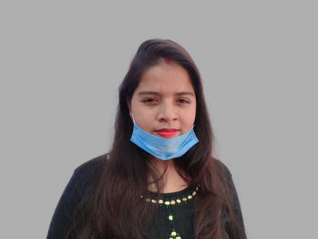 Young asian woman wears mouth face mask, wrong way, incorrect wearing - masks should cover nose and mouth.