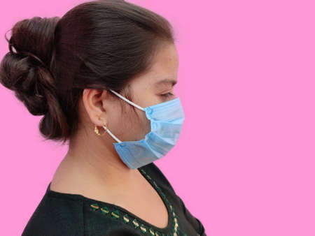 Side view of young indian woman face wearing medical face mask on white background. Protect your health. Coronavirus concept Stock fotó