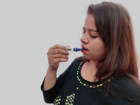 Indian woman with a thermometer in her mouth measures the temperature. Chills, fever and other symptoms of flu and illness on grey background