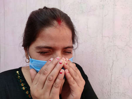 Young Asian woman wearing mask sneeze or cough