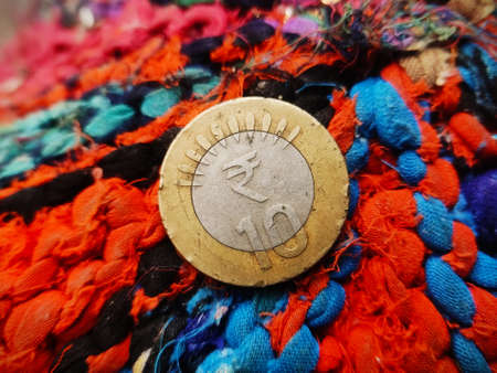 Indian Ten rupee coin placed on colourful Textured Background