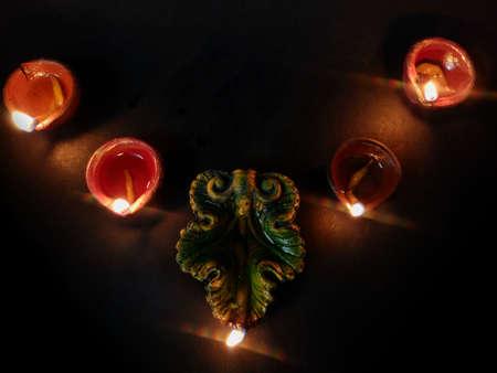 Home decoration using oil lamp or diya arranged in row for Diwali celebrations , selective focus on deep , black background Foto de archivo