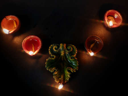 Home decoration using oil lamp or diya arranged in row for Diwali celebrations , selective focus on deep , black background Stock fotó