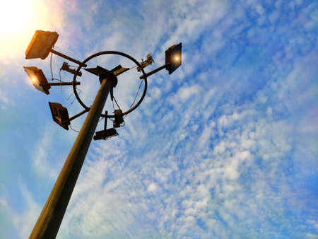 Electric lamp or mast post very high in hight against blue sky used for illumination roads during night Banque d'images