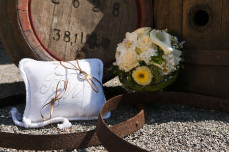 hitched: bridal rings with wedding flowers next to wooden barrels Stock Photo