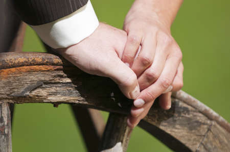 A couple holds their hands at their wedding on a wooden cycle photo