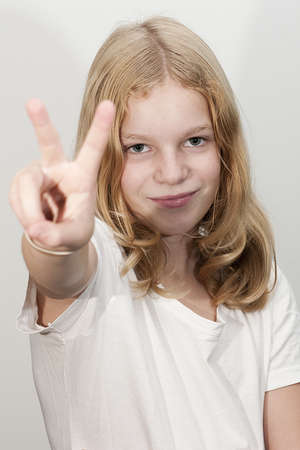 10 11 years: Young blond haired girl gives a peace sign Stock Photo