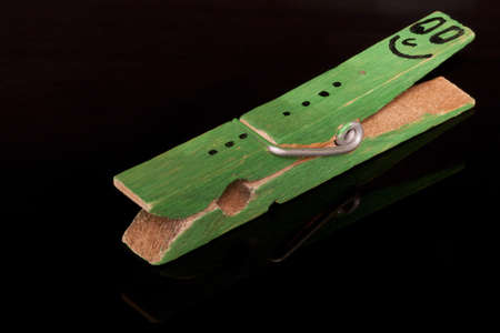 clothes peg: green colored  clothespin with smiley on it