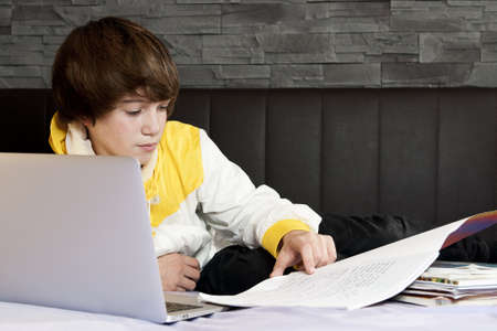 young school teenager makes his homework with notebook and some books on the bed with leader and stone wall in the back