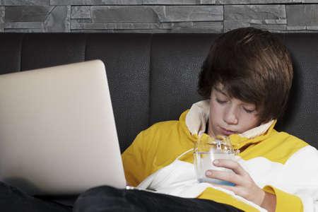 adolescencia: los j�venes se queden dormidos delante de su port�til mientras que el aprendizaje y bebiendo un vaso de agua Foto de archivo