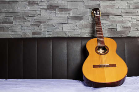 couch: classical guitar lying on the bed in front of a brown leather back and a stone wall