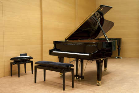 piano de cola: un piano negro listo para jugar con las heces en frente en un escenario de madera Foto de archivo