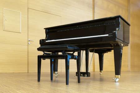 zwarte concert paino staat op een houten podium met kruk klaar voor het spelen van Stockfoto
