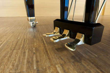 golden piano pedals of a concert grand piano standing on concert stage Standard-Bild