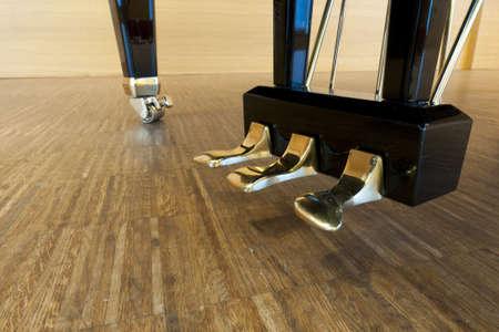 gouden piano pedalen van een concertvleugel staat op concertpodium