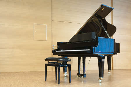 opened black grand piano with stool on a wooden concert stage