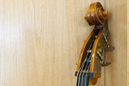 neck of a cello leaning on a wooden wall photo