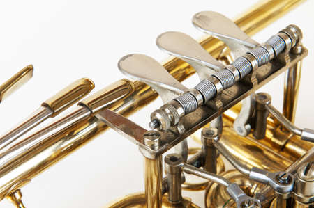 brass band: silver golden trumpet valves in detail view with white background