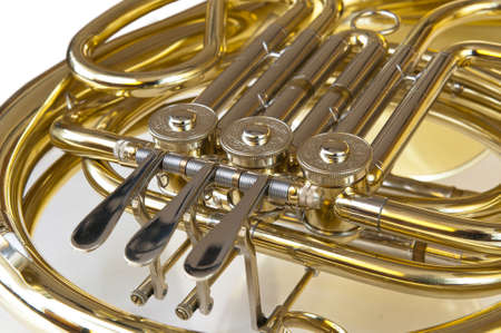 woodwind instrument: detail of brass and silver horn or bugle with valves lying on a white background