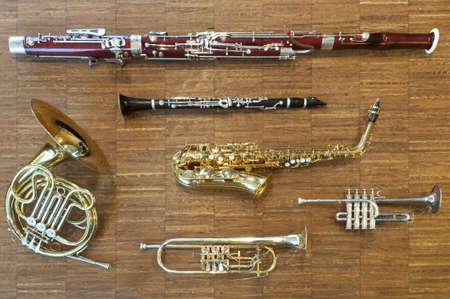 several wind instruments laying on a wooden floor. trumpet, horn, saxophone, clarinet, flute,  bassoon, curtal Standard-Bild