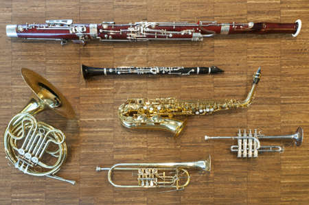 several wind instruments laying on a wooden floor. trumpet, horn, saxophone, clarinet, flute,  bassoon, curtal Stock Photo