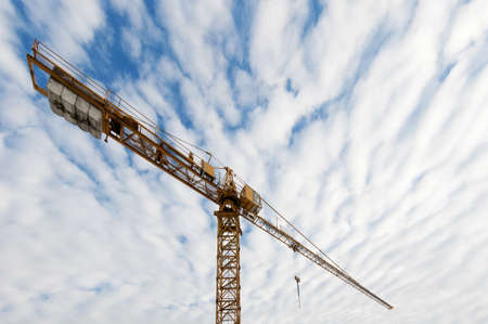 huge tower crane at  a construction site building with blue cloudy sky