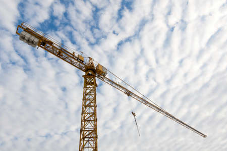 huge orange tower crane with blue cloudy sky in background for a construction site Stock Photo - 11755159