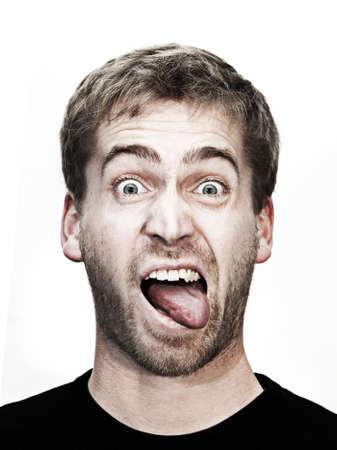 jonge blonde man maakt grimas met de mond wijd open en de tong buiten
