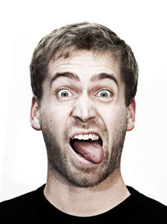 comedian: young blonde man makes grimace with mouth wide open and tongue outside Stock Photo