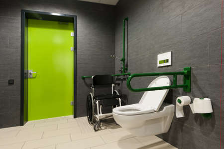 lavatory: a toilet for disabled people with green bars, wheelchair and door