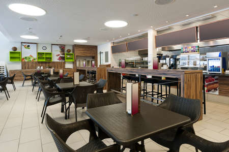 grote zelfbedieningsrestaurant met hout en rotan interieur en een lange bar uitlezing