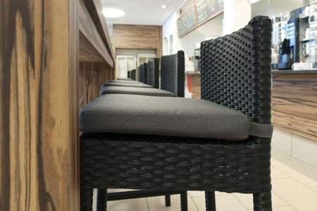 meshwork: aligned high rattan chairs with  seat-contact surface in front of wooden table in self service restaurant