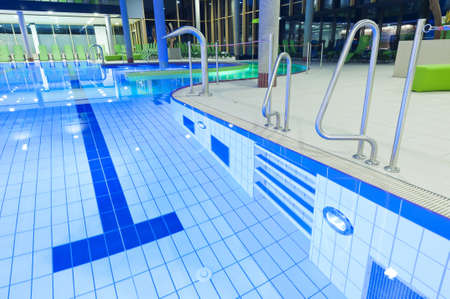 tegels zwembad met helder water en licht met groene banken in de achtergrond
