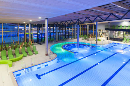 view from the top of a new swimming pool with green divans and lighted water