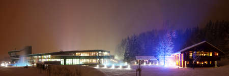 illuminated building of a swimming pool, water slide and sauna chalets and lighted tree photo